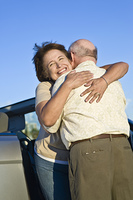 Senior couple standing in front of car and embracing
