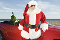 Father Christmas stands by red convertible with Christmas tree