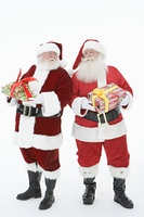 Two men dressed as Santa Claus holding gifts