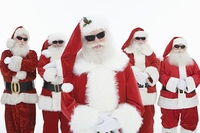 Group of men dressed as Santa Claus wearing sunglasses