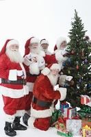 Group of men dressed as Santa Claus decorating Christmas tree