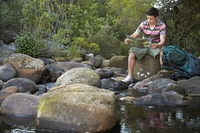 Teenage boy (16-17 years) sitting on stone by river reading map