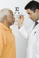 Mid adult doctor examines senior man's eyesight