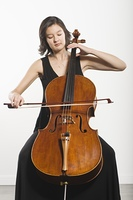 Mixed race cellist sits playing