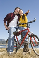 Young couple stand with mountain bike man pointing