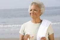 Senior woman stands with drinking water and towel over her shoulder on beach