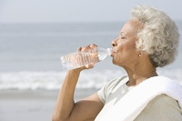 Senior woman stands with drinks water with a towel over her shoulder on beach