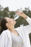 Mid adult woman drinking mineral water