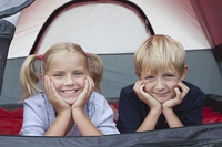 Brother and sister smiling from tent