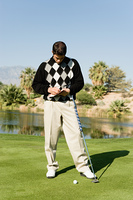 Golfer Marking Scorecard While Standing on Green