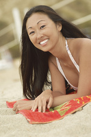 Happy Young Woman Lying on Beach