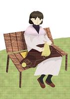 公園のベンチで編み物をする女性