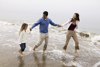 Family walking through surf on beach