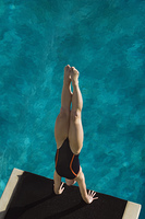 Female swimmer standing on hands on Diving Board