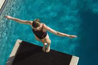 Female swimmer standing on diving board