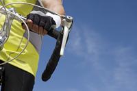 Senior man cycling, close-up of handlebar
