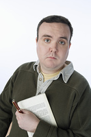 Portrait of mid-adult man holding pen and book