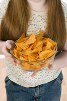 Girl standing, holding bowl of potato chips, mid section