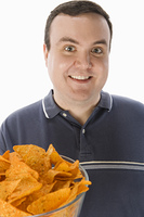 Mid-adult man holding glass bowl of potato chips