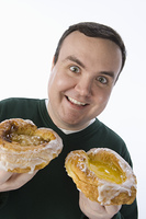 Mid-adult man holding pastry