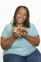 Portrait of Mid-adult overweight  woman holding bowl wit fruit salad and smiling