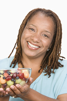 Portrait of Mid-adult overweight  woman holding bowl wit fruit salad and smiling, close-up