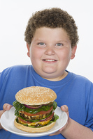 Overweight  boy holding plate with big cheeseburger