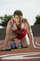 Young man in starting blocks holding relay baton, portrait