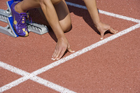 Female athlete in starting block, ready to run