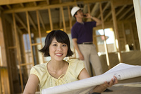 Young woman holding blueprint in construction site