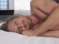Mid-adult man lying on bed, head and shoulders