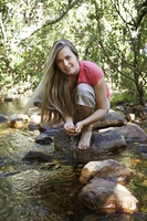 Portrait of teenage girl (16-17 years) squatting on stone by stream in forest, smiling