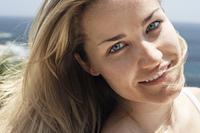 Smiling woman on beach, close-up, portrait