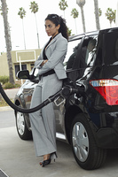 Woman leaning on van with fuel pump in it