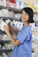 Female nurse standing at shelf with medicines, portrait