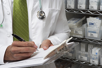 Male doctor writing in patient chart, mid section
