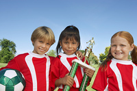 Three children (7-9 years) holding soccer ball and trophy on soccer field, portrait