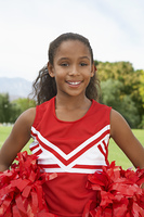 Girl cheerleader (7-9 years) standing on soccer field, portrait