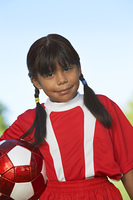 Girl (7-9 years) holding soccer ball under arm, portrait