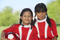 Two girl soccer players (7-9 years) embracing on soccer field, portrait