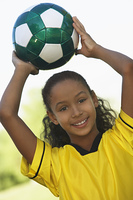 Girl (7-9 years) holding soccer ball above head, portrait