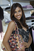 Portrait of young woman with purse at clothes shop