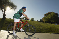 Senior man cycling in park at dusk, side view