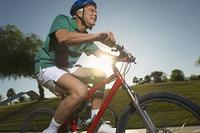 Senior man cycling in park at dusk