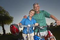 Senior couple on bicycles at dusk, portrait