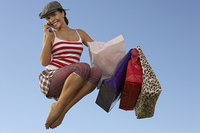 Portrait of young woman jumping with shopping bags, using mobile