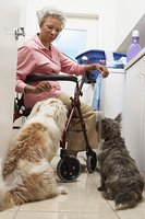 Senior woman doing laundry with dogs
