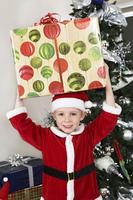 Boy (5-6) in Santa costume holding present over head