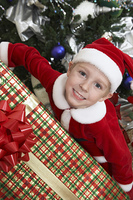 Boy (5-6) in Santa costume holding present by Christmas tree