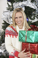 Woman holding presents in front of Christmas tree